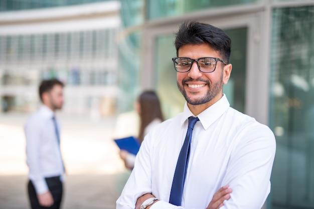 Glimlachende zakenman voor een groep collega's, groepswerkconcept