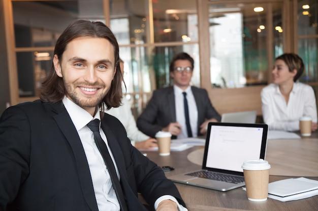 Glimlachende zakenmanmanager die in kostuum camera op vergadering bekijken