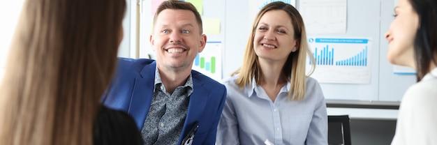 Glimlachende zakenmensen bespreken bedrijfsprocessen in een cirkel terwijl ze op stoelen zitten