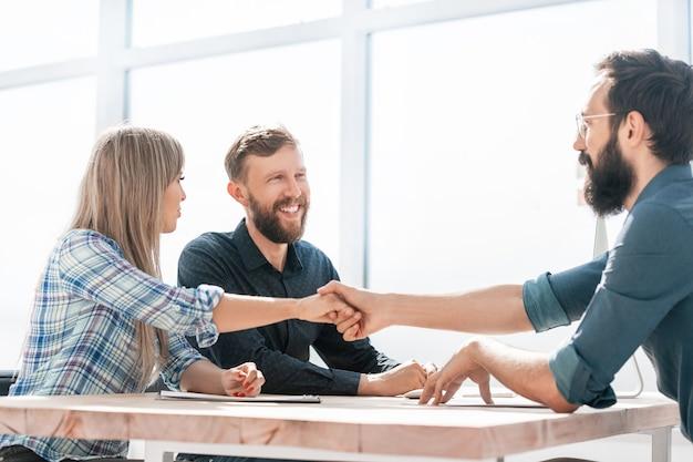 Glimlachende zakenpartners handdruk tijdens een zakelijke bijeenkomst.