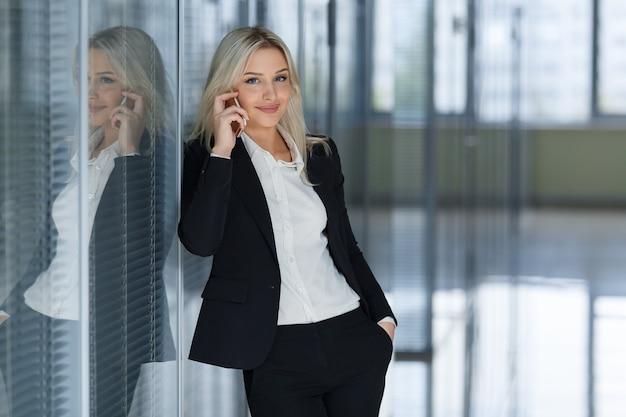 Glimlachende zakenvrouw aan de telefoon die naar de camera in een kantoor kijkt