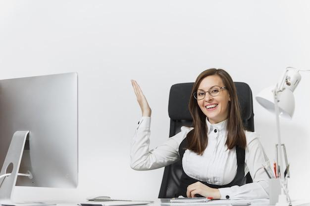 Glimlachende zakenvrouw die aan het bureau zit en op de computer werkt met documenten in een licht kantoor
