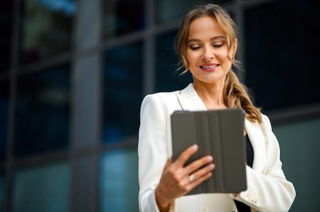 Glimlachende zakenvrouw die een digitale tablet buiten gebruikt