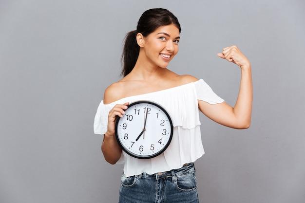 Glimlachende zakenvrouw die klok vasthoudt en biceps toont geïsoleerd op een grijze muur