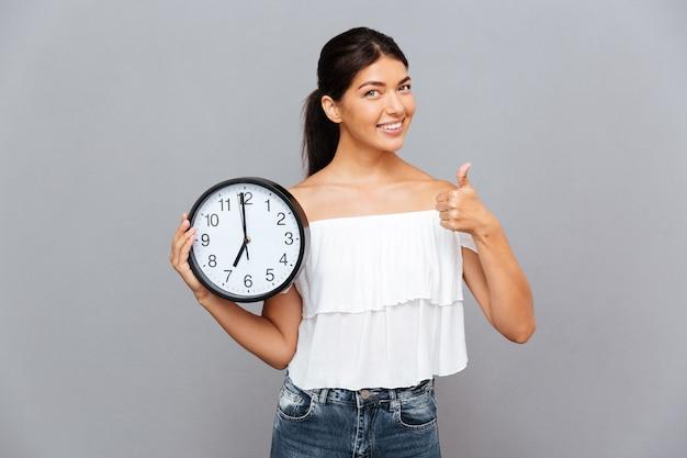 Glimlachende zakenvrouw die klok vasthoudt en duim toont geïsoleerd op een grijze muur