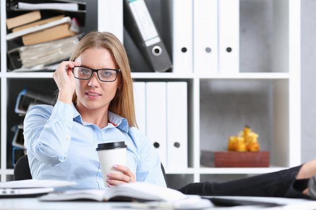 Glimlachende zakenvrouw die koffie drinkt uit een papieren beker