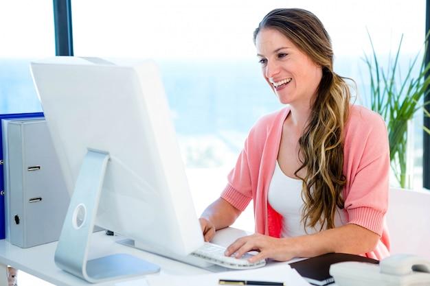 Glimlachende zakenvrouw in haar kantoor, op haar computer