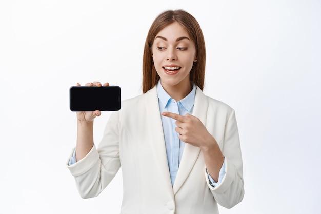 Glimlachende zakenvrouw in professioneel pak, wijst naar lege smartphone, houdt scherm horizontaal, introduceert website of online promo, witte muur