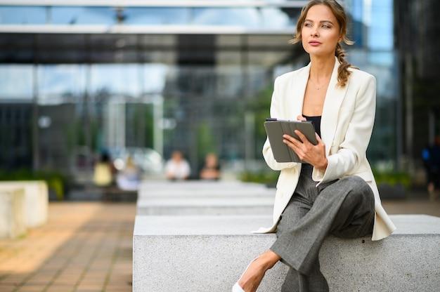 Glimlachende zakenvrouw met behulp van een digitale tablet buiten zittend op een bankje