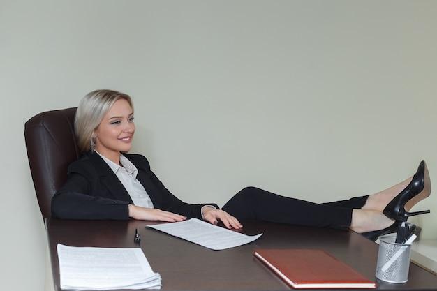 Glimlachende zakenvrouw met haar voet op het bureau