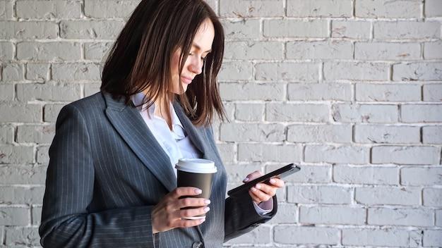 Glimlachende zakenvrouw met korte donkere haartypes op zwarte smartphone met papieren koffiekopje in de buurt van witte bakstenen muur in de ochtend kopieerruimte