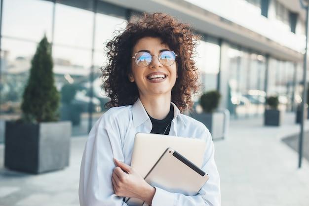 Glimlachende zakenvrouw met krullend haar en bril poseert terwijl ze een aantal moderne gadgets vasthoudt
