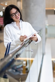 Glimlachende zakenvrouw schrijven papieren lijst maken van aantekeningen in winkelcentrum met positieve emotie