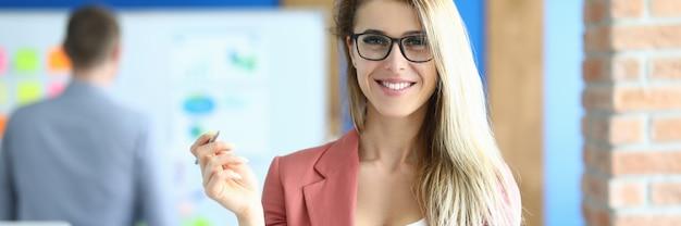 Glimlachende zakenvrouw staat in het kantoor en houdt pen. vrouwencarrière in bedrijfsconcept