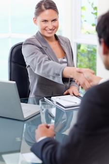 Glimlachende zakenvrouw verwelkomt klant in haar kantoor