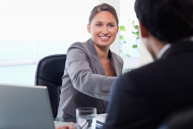 Glimlachende zakenvrouw verwelkomt klant