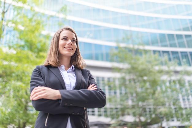 Glimlachende zakenvrouw voor haar kantoor