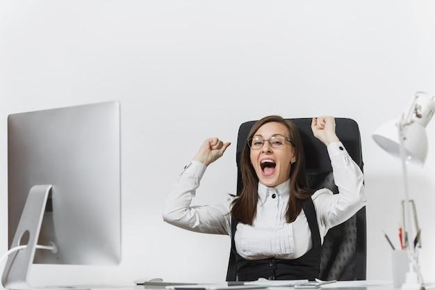 Glimlachende zakenvrouw zittend aan de balie, werken op computer met moderne monitor en documenten op kantoor, zich verheugen over succes, handen omhoog houden, ruimte kopiëren voor reclame