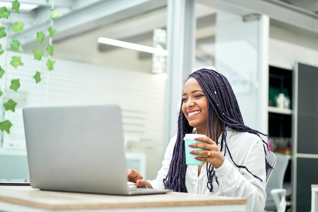Glimlachende zakenvrouw zittend aan een bureau koffie te houden tijdens het werken op laptop