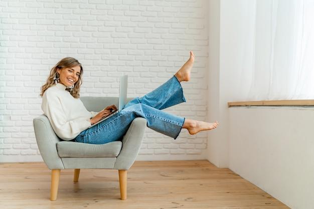 Glimlachende zakenvrouw zittend op de bank thuis werken op laptopcomputer