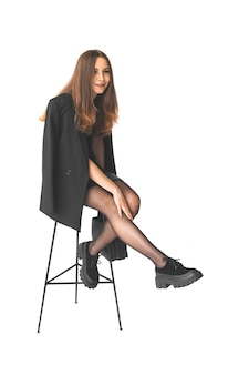 Glimlachende zakenvrouw zittend op een stoel geïsoleerd op een witte achtergrond. vrouw in zwarte jurk met zwarte leren tas, stijlvolle mode concept foto