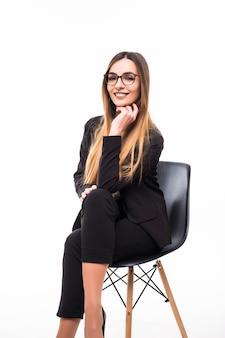 Glimlachende zakenvrouw zittend op een zwarte stoel op wit