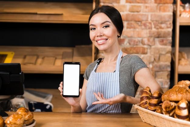 Glimlachende zekere vrouwelijke bakker bij de bakkerij tegen het tonen van mobiele telefoonvertoning