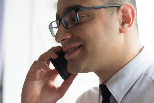 Glimlachende zekere zakenman die aan partner spreekt