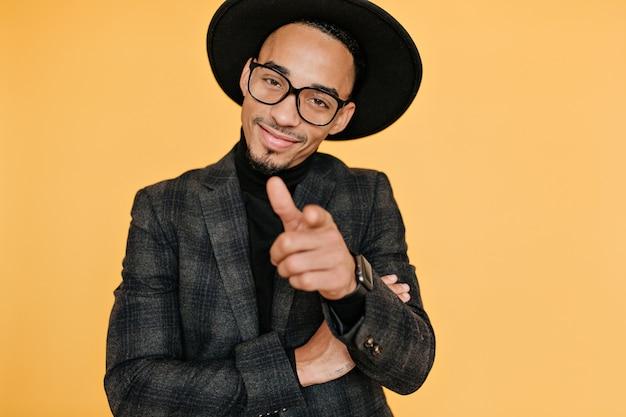 Glimlachende zelfverzekerde afrikaanse man wijzende vinger. portret van knap mannelijk model met bruine huid dat op gele muur wordt geïsoleerd.
