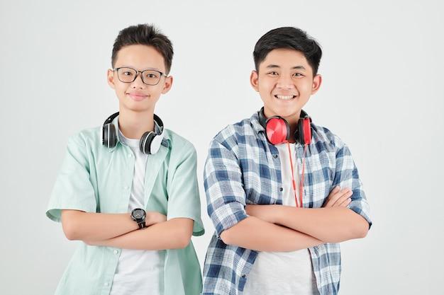 Glimlachende zelfverzekerde aziatische schooljongens die wapens vouwen en kijken