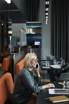 Glimlachende zelfverzekerde blanke zakenvrouw in bril die aan tafel zit met notitieblok en gezichtsmasker en telefonisch praat terwijl ze in café werkt