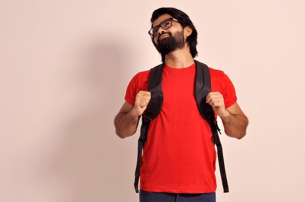 Glimlachende zelfverzekerde jonge, bebaarde knappe student houdt rugzak vast met beide handen omhoog kijkend
