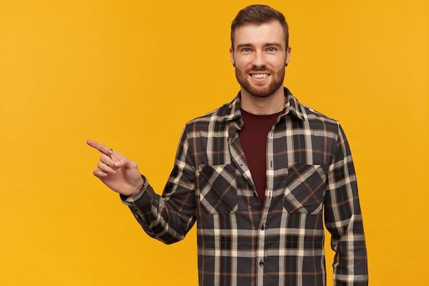 Glimlachende zelfverzekerde jonge bebaarde man in geruite overhemd permanent en wijzend weg naar lege ruimte door vinger over gele muur kijkend naar voorzijde