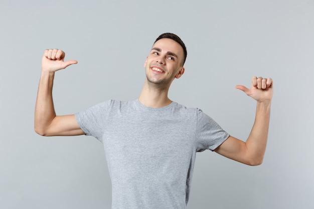 Glimlachende zelfverzekerde jongeman in vrijetijdskleding die opzij kijkt en duimen op zichzelf toont