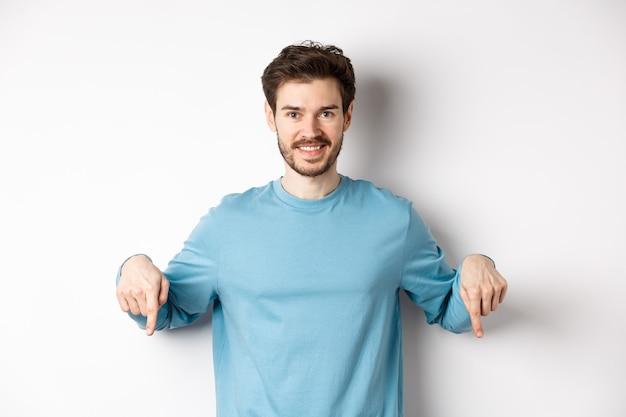 Glimlachende zelfverzekerde man wijzende vingers naar beneden, promo banner of logo tonen op witte achtergrond, staande in casual blauw sweatshirt.