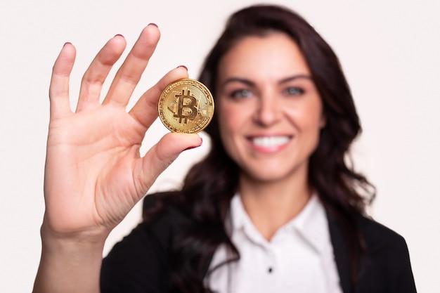 Glimlachende zelfverzekerde vrouw die bitcoin munt toont