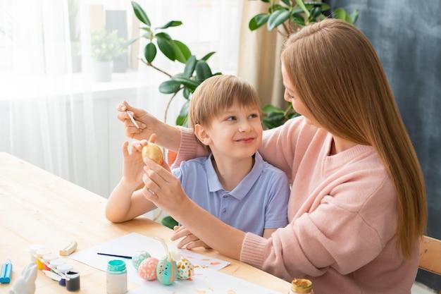 Glimlachende zoon die moeder bekijkt terwijl zij thuis paasei in zijn hand schildert