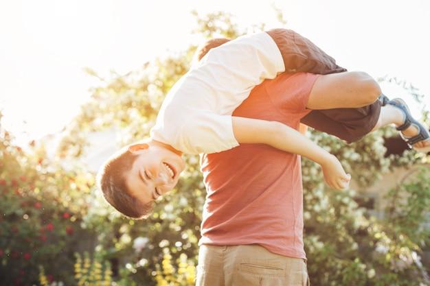 Glimlachende zoon en vader die pret in park hebben