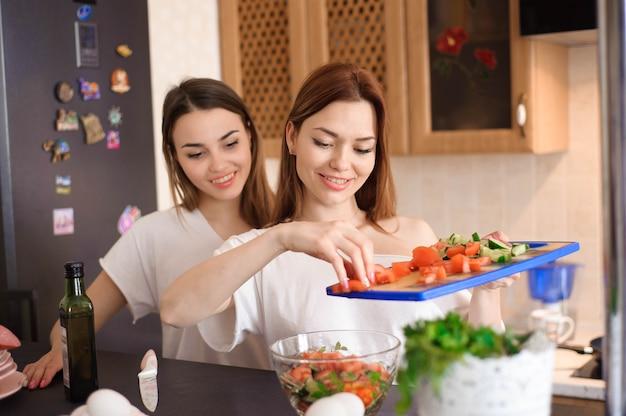 Glimlachende zusters die diner samen in de keuken voorbereiden.