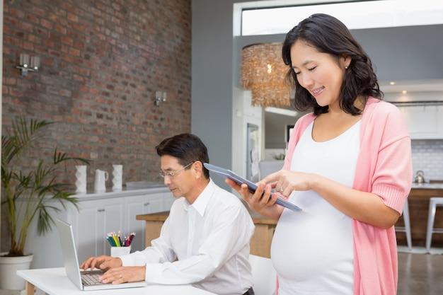 Glimlachende zwangere vrouw die tablet thuis gebruiken terwijl de echtgenoot aan laptop1 werkt