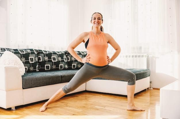 Glimlachende zwangere vrouw die zich in driehoek met handen op heupen bevindt huisbinnenland.
