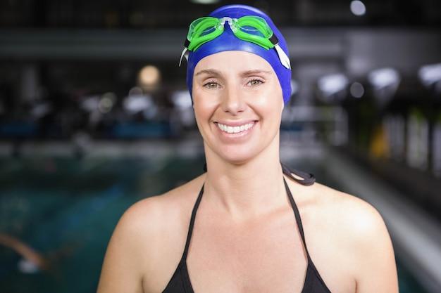 Glimlachende zwangere vrouw die zich naast het zwembad op het vrije tijdscentrum bevindt