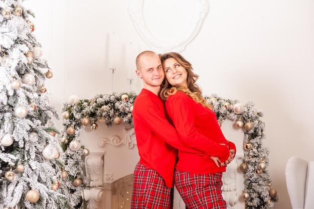 Glimlachende zwangere vrouw en man hebben thuis plezier met kerstinterieur
