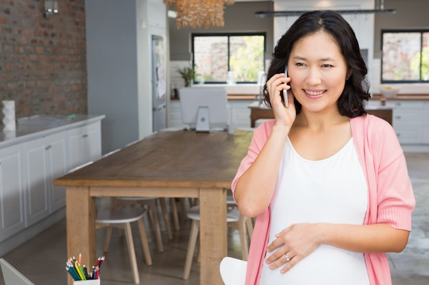 Glimlachende zwangere vrouw op een telefoongesprek thuis
