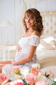 Glimlachende zwangere vrouw zittend op bed en buik knuffelen