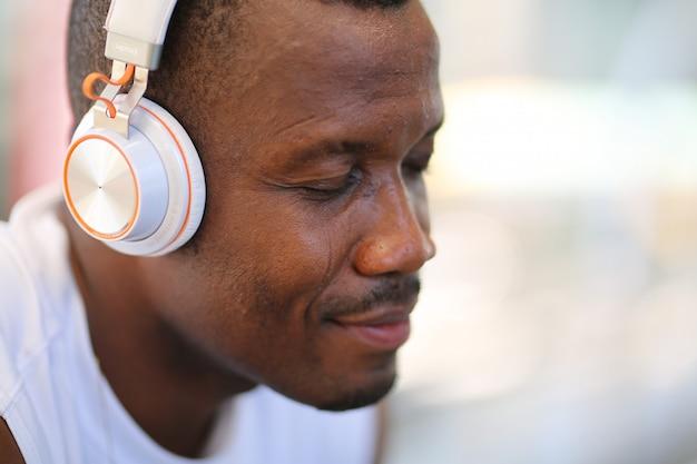 Glimlachende zwarte huidmens het luisteren muziek over hoofdtelefoons