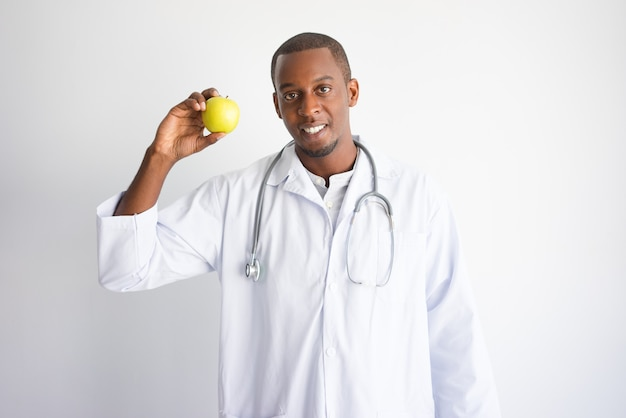 Glimlachende zwarte mannelijke arts die en appel tonen aanbevelen.