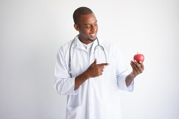 Glimlachende zwarte mannelijke arts die en op rode appel houdt richt.