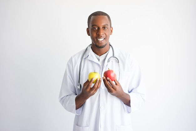 Glimlachende zwarte mannelijke arts die gele en rode appel houdt.