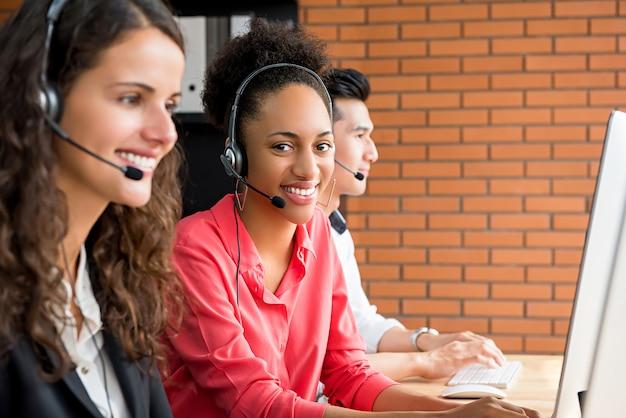 Glimlachende zwarte vrouwelijke telemarketing klantenserviceagent die in call centre werkt